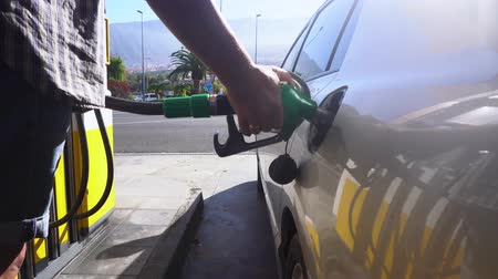 galão : person starts refueling car, scene on gasoline station