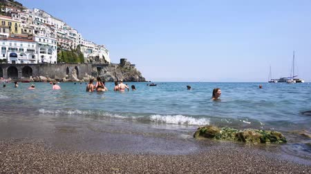 amalfitana : AMALFI, ITALY - JULY 14, 2017: People swimming and enjoying sea at Amalfi town beach and Tyrrhenian sea waters, Italy