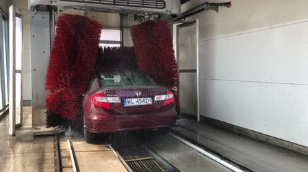 muck : WARSAW, POLAND - APRIL 30, 2018 red car is being washed in automatic car wash