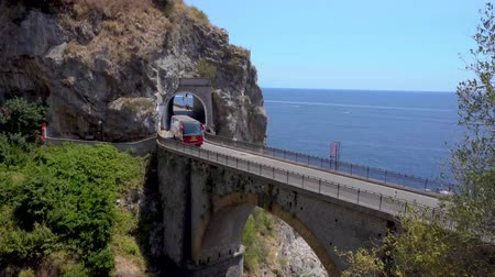 abyss : AMALFITANA, ITALY - JULY 14, 2018: bus driving on picturesque road viaduct over sea of Amalfi coast, Italy Stock Footage