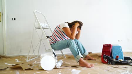 remodelar : Painting Equipment in the room and discouraged women having problems with renovations