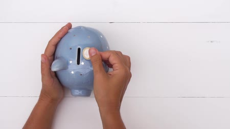 patting : Someones hand putting coin and patting piggy bank on white background, savings concept