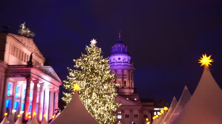 adwent : Gendarmenmarkt Christmas market kiosks in Berlin illuminated at night, Germany, showing christmas tree closer