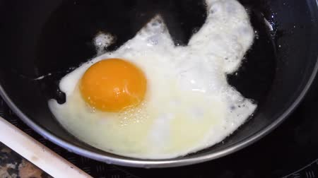 Cooking egg in black pan, someone hand adding salt Стоковые видеозаписи