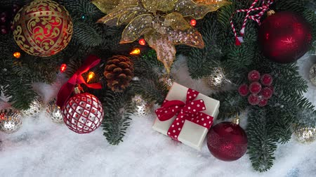 Christmas evergreen tree decorated with golden and red balls and glowing garland in snow