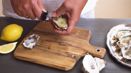 istiridye : someones hands open fresh raw oysters