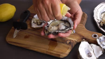 bivalve : someones hands squising lemon on fresh raw oysters Stock Footage