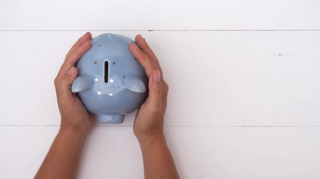 impostos : Someones hand holding and patting piggy bank on white background, savings concept Stock Footage