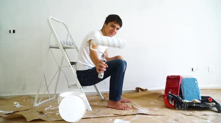 remodelar : Painting Equipment in the room and young men with paint roller doing renovations