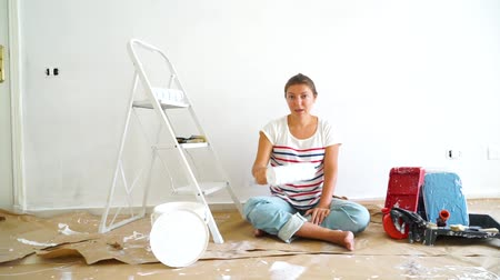remodelar : Happy women in the room showing paint roller Stock Footage
