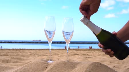 flet : champagne on beach - someones hands opening bottle and pouring drink into the glasses Wideo
