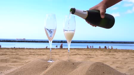 champagne on beach - someones hands pouring drink into the glasses, slow motion