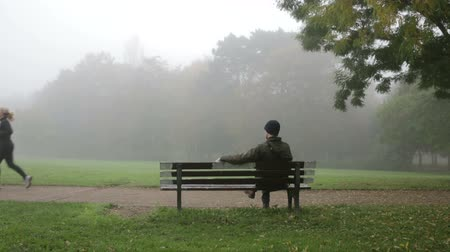 один человек : man sitting on bench in park and thinking about his life