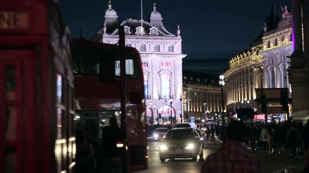 londra : Piccadilly Circus in London at NIght with crowd of people in the background. Nightlife in London Stok Video