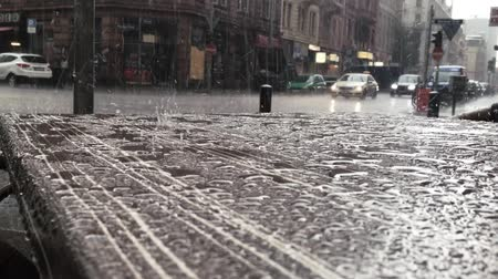andar : rain in city situations with cars and people walking in the background