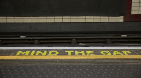 mind the gap : London underground train approaching platform with people departing and getting on the tube