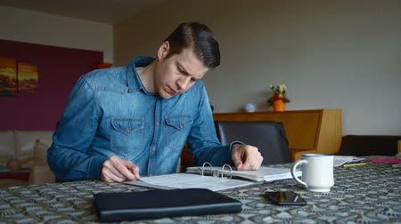 banknoty : Man at home calculating the bills and looking Concerned