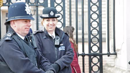 Лондон : London, United Kingdom - March 22, 2015: two police officers in London at Buckingham Palace in good mood. Lots of spectators wait for the change of guards.