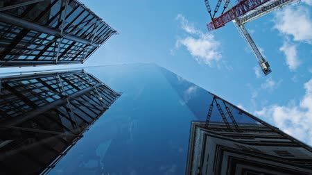 glass structure : Modern building with a glass fassade in urban environment. the surrounding buildings and clouds from the sky reflect in the windows. construction site next to the tae modern reflecting on glass fassade. Blue sky with few clouds. Stock Footage