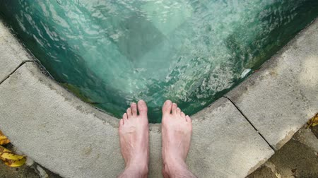 male : A Man standing next to the pool and watching the ripples in the water created by the wind. The corner of a swimming pool with turqouise water. Focus on the feet and the view from the persons perspective.