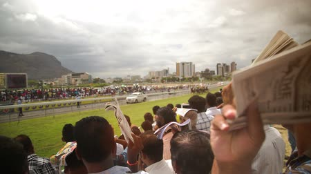 horse racing : Spectators at the mauritian turf club watch the horses run by and protect themselves from the sun. The crowd is mainly male dominated, but you also have kids and women watching.