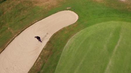 поле для гольфа : Aerial perspective of a player hitting a golf ball out of a sand trap at a golf course in Germany