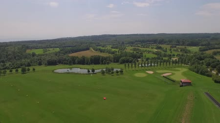 clubhouse : A drone flies above a golf course filming the landscpae around on a sunny day.