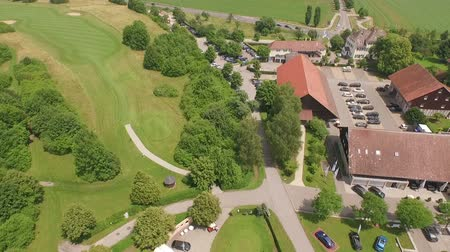 clubhouse : A drone flies above a golf course and the landscape around