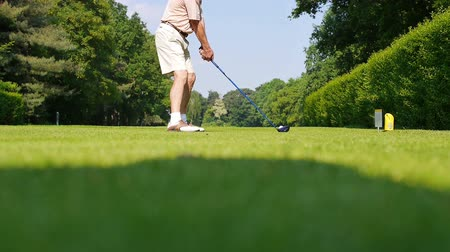 поле для гольфа : An elder one in shorts playing a drive on a sunny day at a golf course.