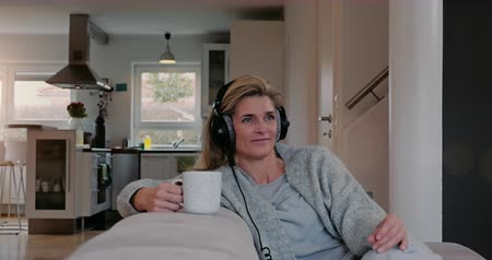 contentamento : Contented woman relaxing on a sofa at home listening to music on stereo headphones with a happy smile and her eyes closed in bliss with copyspace