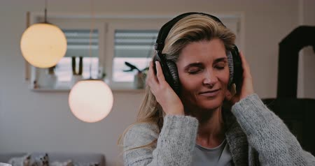наушники : Attractive woman enjoying her music indoors at home as she listens to the soundtracks on stereo headphones with her eyes closed and a smile of pleasure