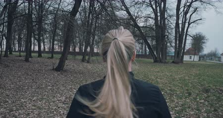 arkasında : Rear view of a fit woman in black sportswear with a blond ponytail running outdoors in a park in a healthy lifestyle concept with copyspace