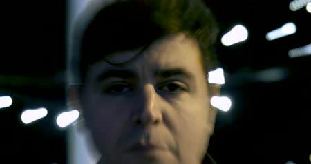 rústico : The camera zooms in and out of a mans face standing behind bright night lights. The lights appear to be pulsating because of the cameras movement. Stock Footage