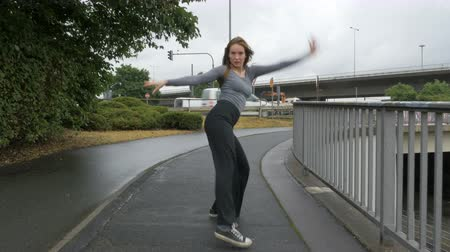 uliczki : A young woman performs a street dance on a bridge sidewalk during a rainy wet day and walks away. The dancer moves towards the camera. Wideo