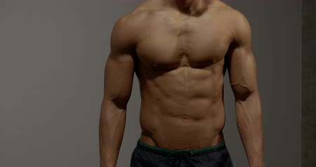 abs : The torso of a fitness model. He stands still while tapping and touching his stomach muscles.