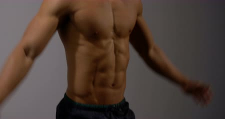 abs : A body builder does jumping jacks in from the camera. Filmed behind a grey background.