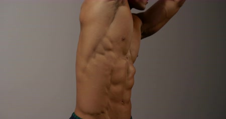 abs : A male fitness model displays his muscular torso by stretching his arms upwards. The shot is focused on his torso as he engages in the display of physique.