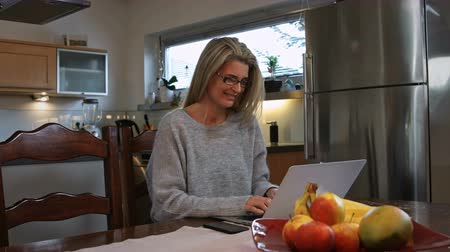 resumes : A woman working at home on her computer smiles for the camera and resumes working. Stock Footage