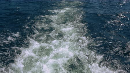 prędkość : A motorboat causes a trail of foam and bubbles as it stirs the water of Lake Huron. Overhead.
