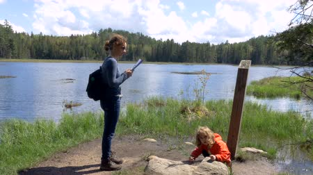 Онтарио : A mother standing and reading a map while her daughter plays with a pine twig. A gorgeous Canadian cottage country nature panorama behind them. Long shot.