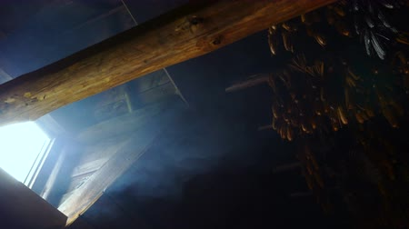 натюрморт : A still life of a corn hanging upside down from a beam. Smoke drifts out a small window in the cabin.
