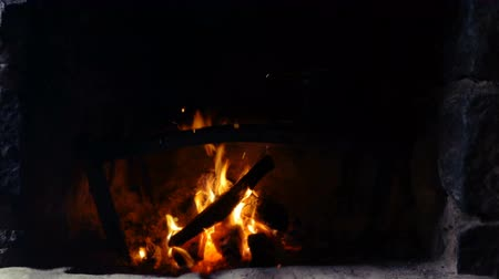 ember : A fire burns in a stone fireplace. Close up.
