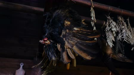 mech : A still life of a rooster hanging upside down from a beam with dried herbs. Close up.