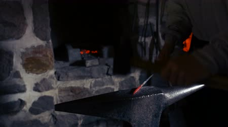 żelazko : Ontario, Canada. May, 2017. A Blacksmith hammers a heated piece of glowing metal. Blacksmiths produce a diverse range of items, from cooking utensils to weapons and light fixtures.