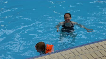 filha : A mother and daughter swim together in an indoor pool.