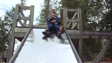 filha : A mother sits on a slide with her small daughter in her arms. Low angle. Vídeos