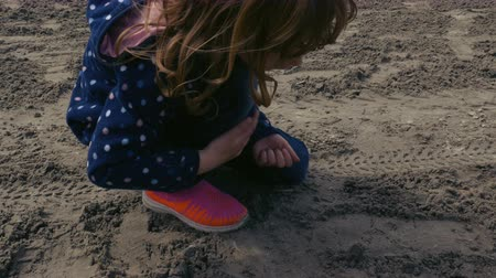 ajoelhado : A little girl kneeling down plays with the wet sands of Lake Ontario. Close up.