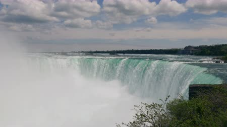fenomen : Mist rises as the waters of the Niagara River violently stirred by the mighty drop from the Horseshoe Falls. Stok Video