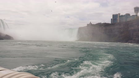 fenomen : A boat of sightseers sails into the mists of the Horseshoe Falls, Niagara.