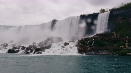 fenomen : Filming the largest waterfall in Niagara. Sightseers in yellow raincoats stand underneath. Close up.